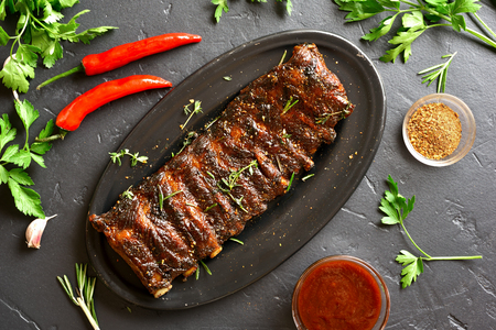 Grilled spare ribs on plate over black stone background. Tasty bbq meat. Top view, flat lay Reklamní fotografie