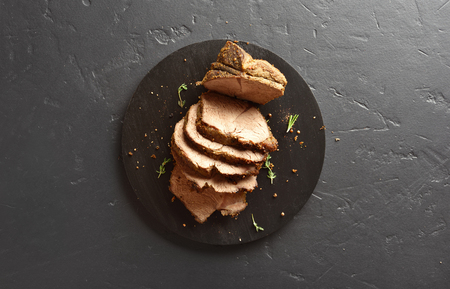 Sliced grilled roast beef on wooden board over black stone background with copy space. Top view, flat lay