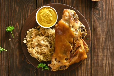 Close up of roasted pork knuckle (eisbein) with braised cabbage (sauerkraut) and mustard on wooden background. Top view