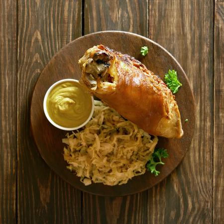 Pork knuckle (eisbein) with braised cabbage (sauerkraut) and mustard on wooden background. Top view Stock Photo