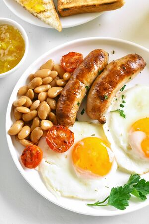 Fried eggs, sausages, beans, tomatoes, greens on plate over white stone background. Top view