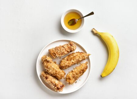 Deep fried bananas on plate over white stone background. Tasty dessert from pan fried bananas in asian style. Top view, flat lay