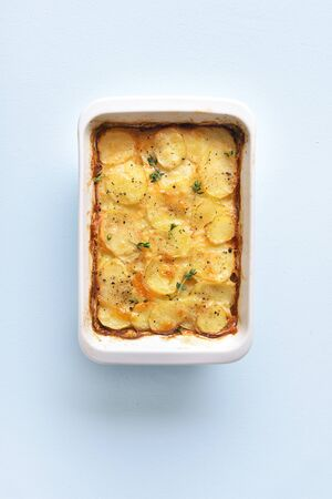 Potato gratin in baking dish over blue stone background with free space. Top view, flat lay