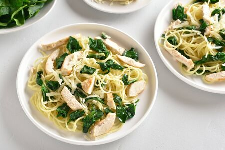 Pasta, spaghetti with spinach leaves, slices grilled chicken breast and grated cheese on plate over white stone table. Tasty pasta with vegetable leaves, healthy food. Stok Fotoğraf