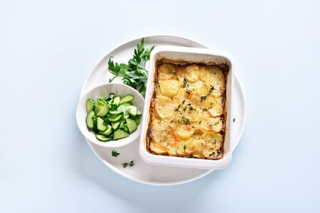 Potato gratin in baking dish over blue stone background.