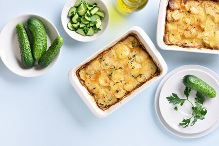 Potato gratin in baking dish over blue stone background. Top view, flat lay