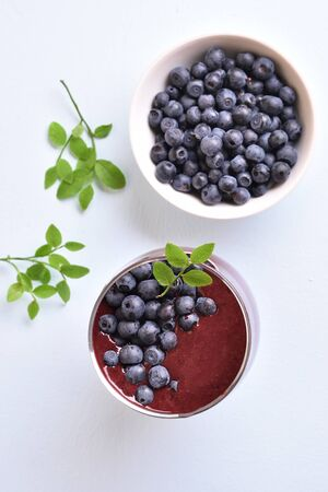 Blueberry smoothie in glass and fresh berries in bowl on light stone background. Top view, flat lay