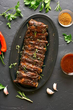 Spicy hot grilled spare ribs on plate over black stone background. Tasty bbq meat. Top view, flat lay Zdjęcie Seryjne