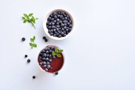 Tasty healthy blueberry smoothie in glass and fresh berries on light stone background with copy space. Top view, flat lay