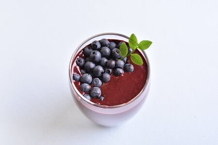 Blueberry smoothie in glass on light stone background. Healthy natural beverage.