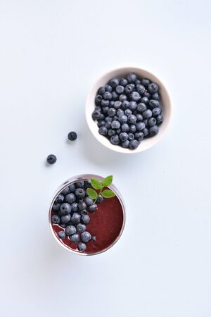 Healthy natural beverage. Blueberry smoothie in glass on light stone background. Top view, flat lay