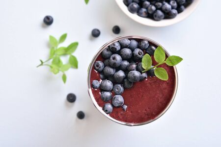 Blueberry smoothie in glass on light stone background. Healthy natural beverage. Top view, flat lay