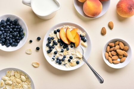 Diet healthy breakfast concept. Oatmeal porridge with peach slices, almond and wild blueberries in bowl over light stone background. Top view, flat lay Stock Photo