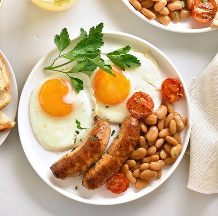 Nahaufnahme des Frühstücks mit Spiegeleiern, Würstchen, Bohnen, Tomaten, Grüns auf Teller über weißem Steinhintergrund. Ansicht von oben, flach Standard-Bild
