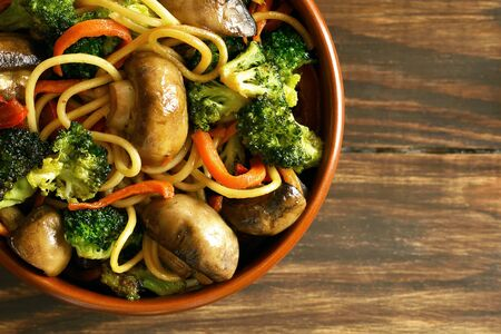 Close up of egg noodles with vegetables in bowl. Cooked food in wok in east style on wooden table. Top view, flat lay Banco de Imagens