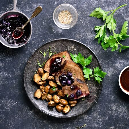 Tasty boiled beef with mushrooms and blueberry sauce on dark stone background. Stewed meat with mushrooms and sweet sauce. Top view, flat lay