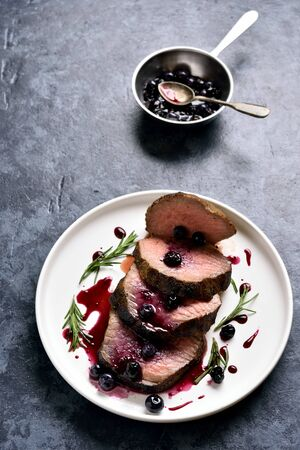 Tasty medium rare roast beef with berry sauce. Sliced grilled beef with blueberry sauce on white plate over blue stone background.
