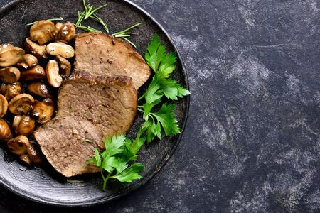Close up of slow cooked beef with mushrooms on dark stone background with free space. Tasty stewed meat with mushrooms. Top view, flat lay Stock Photo