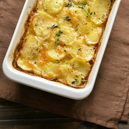 Close up potato gratin in baking dish over wooden background. Top view