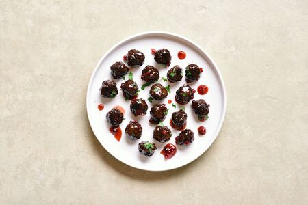 Meatballs with cranberry sauce on white plate over light stone background with free space. Stewed meatballs in sweet berry sauce. Top view, flat lay Stock Photo