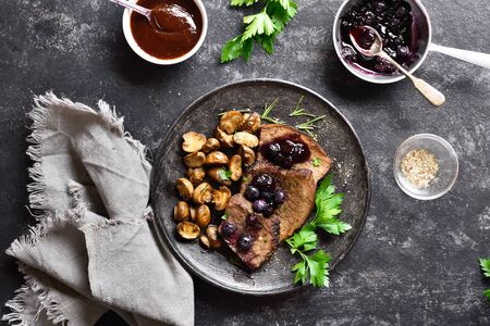 Beef with mushrooms and blueberry sauce on dark stone background. Tasty stewed meat with mushrooms and sweet sauce. Top view, flat lay