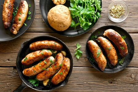 Fried sausages in frying pan over wooden background. Top view, flat lay