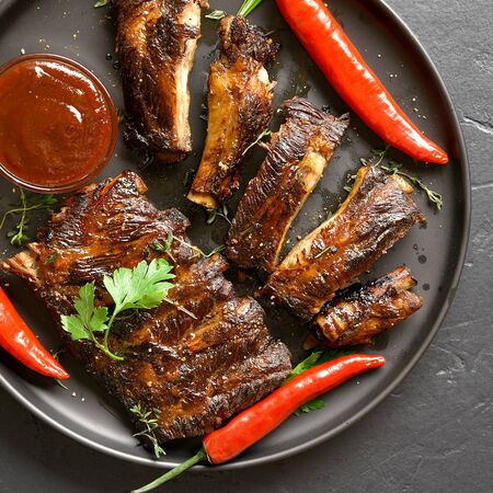 Close up of spicy hot grilled spare ribs on plate over black stone background. Tasty bbq meat. Top view, flat lay Stock Photo