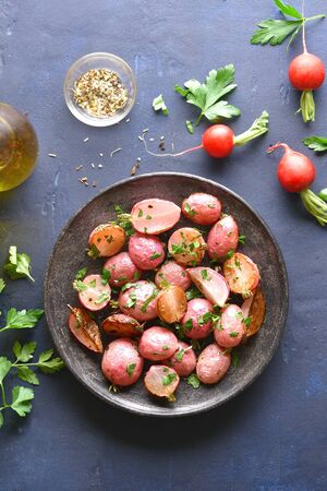 Roasted radish on plate over blue stone background. Top view, flat lay Stock Photo