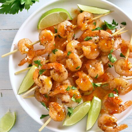 Prawns skewers with greens, spices, lime and sauce on white plate over wooden table. Grilled shrimp skewers. Tasty seafood. Top view, flat lay.  Stok Fotoğraf