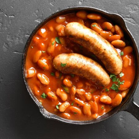 Grilled sausages with baked white beans in tomato sauce in frying pan over black stone background. Top view, flat lay Stock Photo