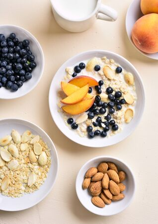 Oats porridge with apricot slices, almond and wild blueberries in bowl over light stone background. Healthy diet breakfast. Top view, flat lay Stok Fotoğraf