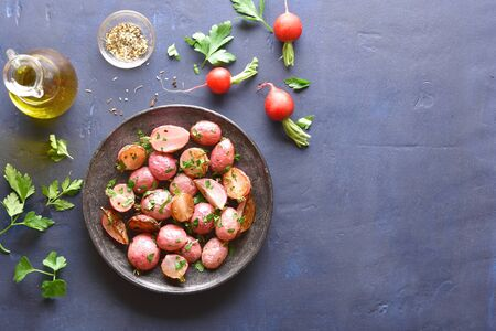 Roasted radish on plate over blue stone background with copy space. Top view, flat lay