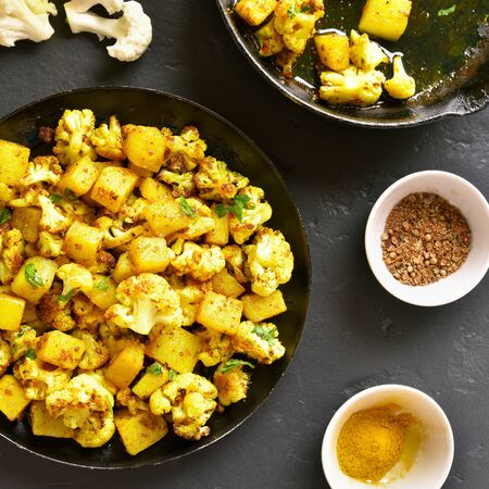 Fried cauliflower with potatoes in frying pan on black stone background. Aloo Gobi indian dish. Top view, flat lay Stock Photo