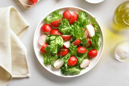Vegetarian vegan or natural organic food concept. Radish salad with lettuce leaves in bowl over white stone background. Vitamin spring salad from fresh vegetables. Top view, flat lay