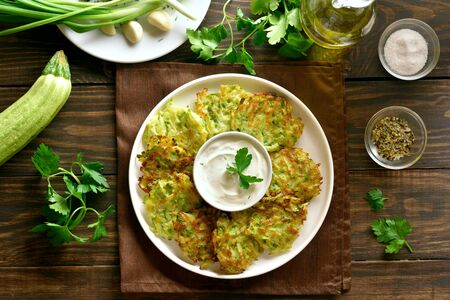 Zucchini fritters with sauce on white plate over wooden background. Vegetarian food. Top view, flat lay