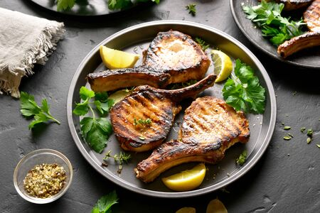 Grilled pork steaks with greens and lemon on plate over black stone table Stock Photo