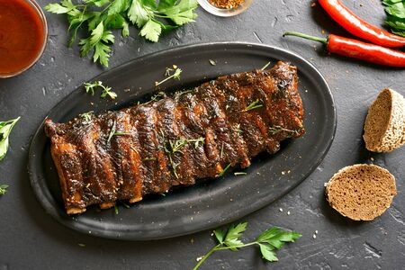 Grilled spare ribs on plate over black stone background. Tasty bbq meat. Top view Stock Photo