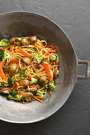 Udon stir-fry noodles with vegetables in wok pan on black stone background. Top view, flat lay 写真素材