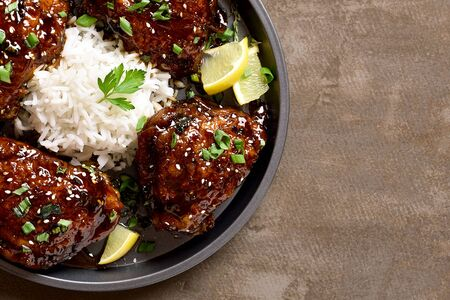 Sweet and spicy honey grilled chicken thighs with rice over dark stone background with free space. Tasty food in asian style. Top view, flat lay