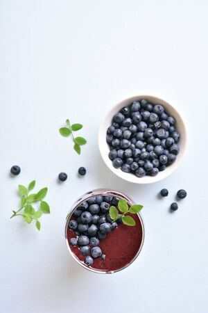 Blueberry smoothie in glass on light stone background with copy space. Healthy natural beverage. Top view, flat lay