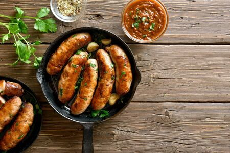Fried sausages in frying pan over wooden background with free text space. Top view, flat lay
