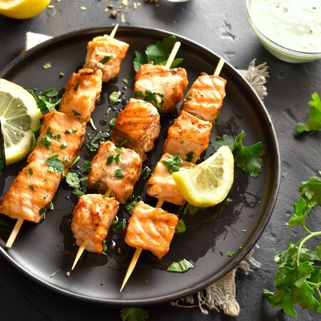 Close up of grilled salmon kebab. Barbecue salmon skewers on black stone background.