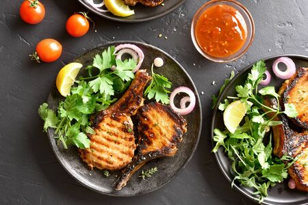 Grilled pork steaks with greens on plate over black stone table. Top view, flat lay