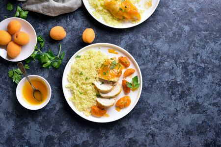 Chicken breasts in apricot sauce and couscous on white plate over blue stone background with copy space. Tasty healthy stewed chicken meat with garnish. Top view, flat lay