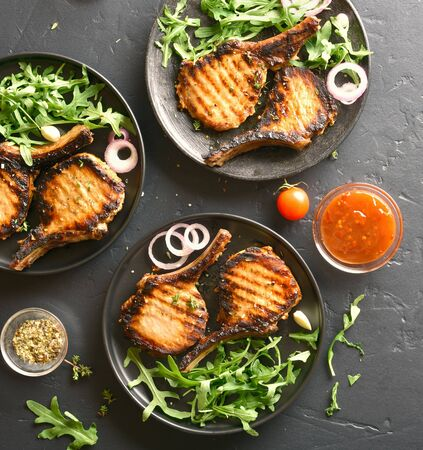 Tasty grilled pork steaks over dark stone background. Top view, flat lay Stock Photo