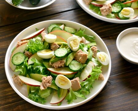 Close up of tuna salad with slices of cucumber, avocado, red apple and eggs in bowl on wooden background. Healthy diet food.