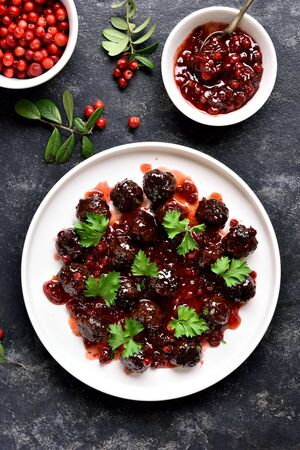 Meatballs with cranberry sauce on white plate over dark stone background. Stewed meatballs in sweet berry sauce. Top view, flat lay Stock Photo