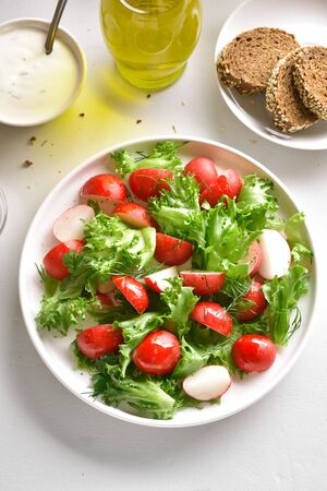 Radish salad with lettuce leaves in bowl over white stone background. Vitamin spring salad from fresh vegetables. Top view