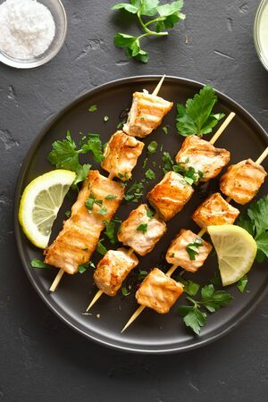 Grilled salmon kebab. Barbecue salmon skewers on black stone background. Top view, flat lay