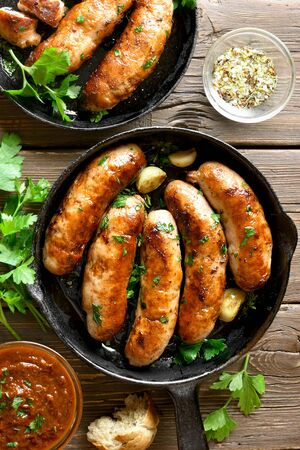 Close up of fried sausages in frying pan over wooden background. Top view, flat lay Stock Photo